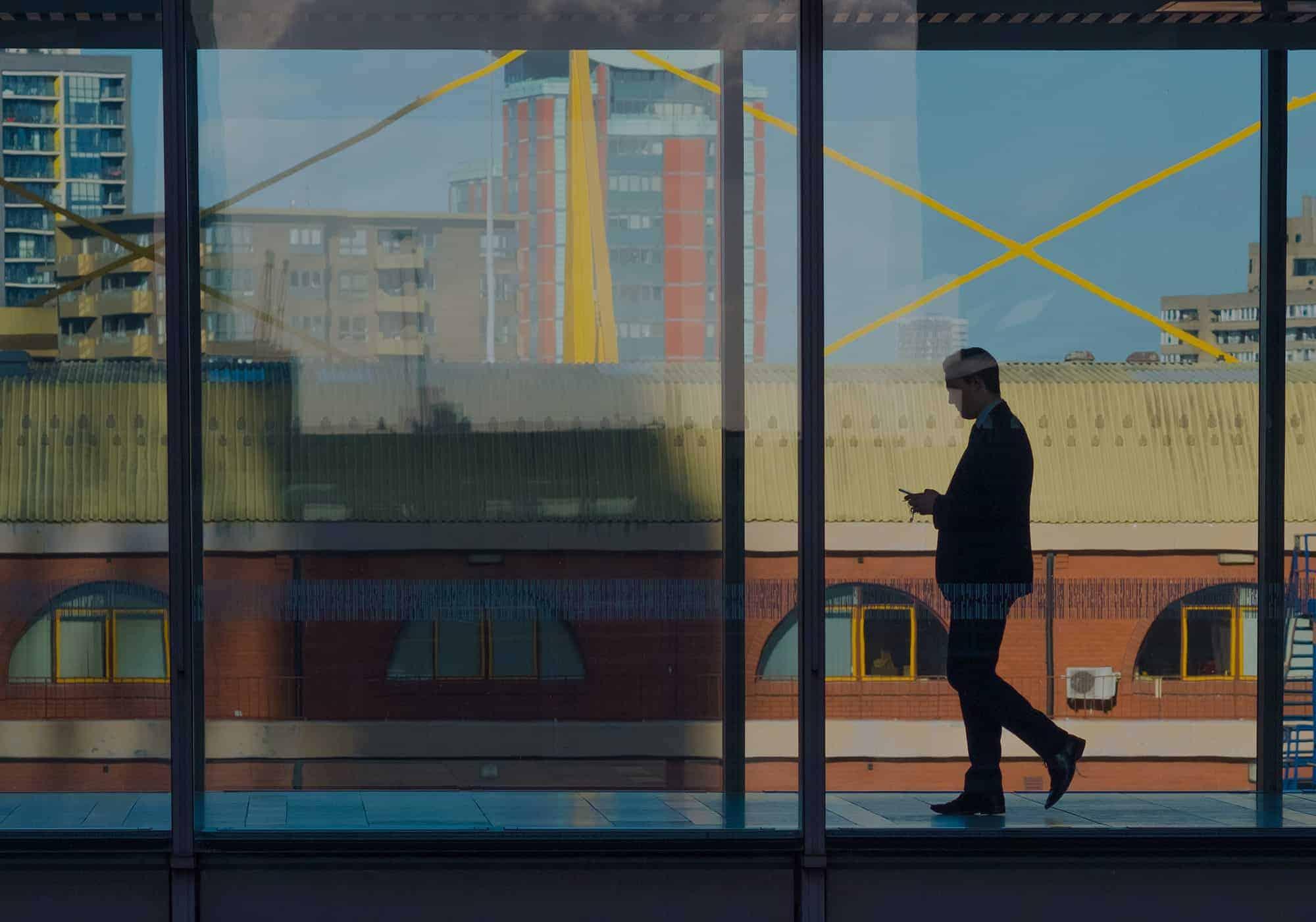 Silhouette dans une gare marchant un téléphone à la main
